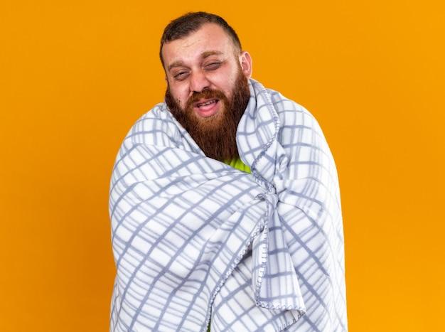 Uomo barbuto malsano avvolto in una coperta che si sente male e soffre di freddo in piedi sul muro arancione
