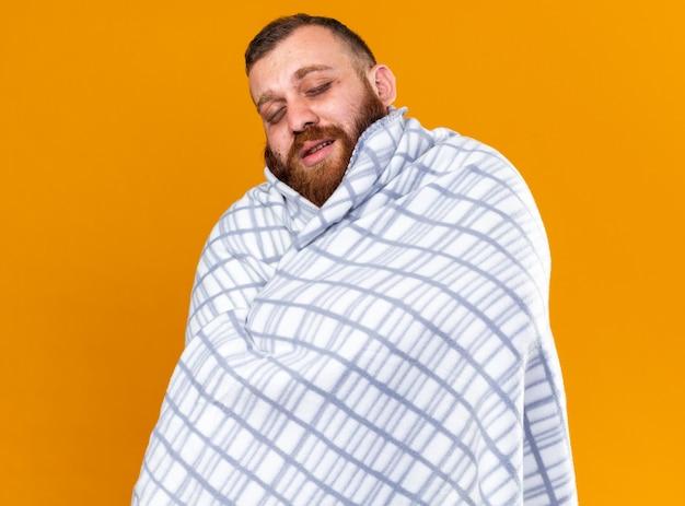 Uomo barbuto malsano avvolto in una coperta che si sente male soffre di freddo con gli occhi chiusi in piedi sul muro arancione orange