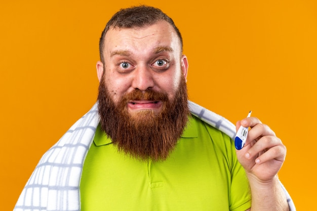 건강에 해로운 수염 난 남자는 온도계를 사용하여 온도를 확인하는 감기에 고통을 느끼는 담요에 싸여 오렌지 벽 위에 서있는 걱정스러운 모습을 보입니다.