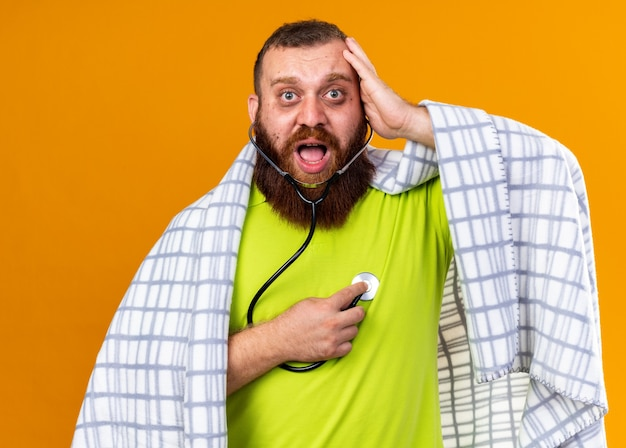 무서워하는 청진기를 사용하여 심장 박동을 듣고 감기로 고통받는 담요에 싸인 건강에 해로운 수염 난 남자