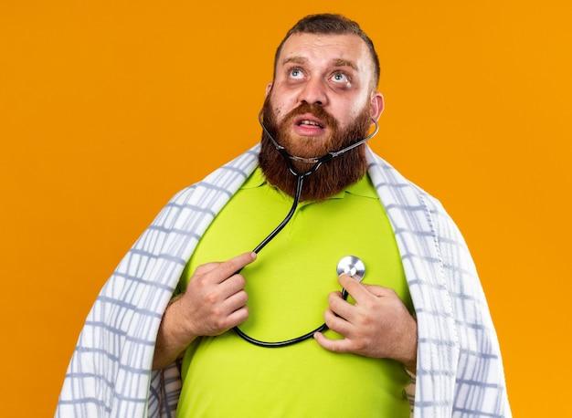건강에 해로운 수염 난 남자는 청진기를 사용하여 심장 박동을 듣고 감기에 걸려 아픈 느낌을 담요에 싸서 오렌지 벽 위에 서있는 걱정을합니다.