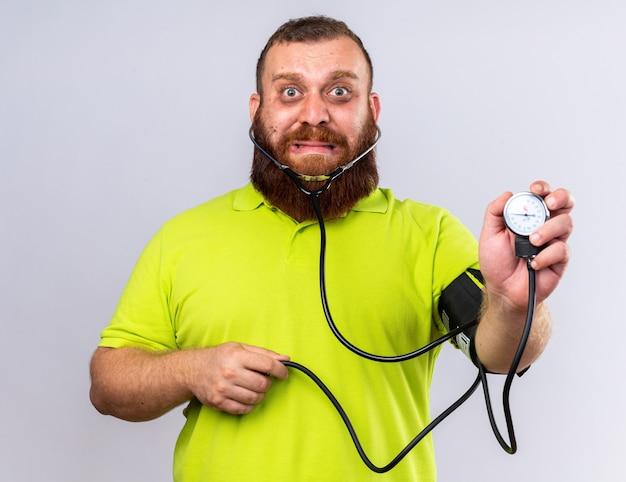 Uomo barbuto malsano in polo gialla che si sente male misurando la pressione sanguigna usando il tonometro che sembra preoccupato in piedi sul muro bianco