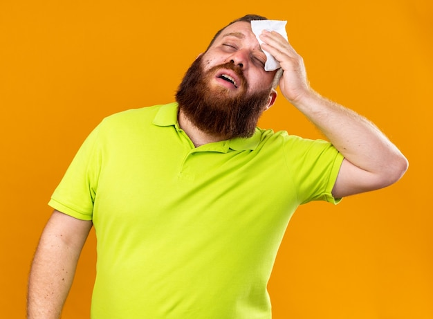 Uomo barbuto malsano in polo gialla che si sente terribilmente soffre di raffreddore e febbre che tiene il tessuto sulla fronte