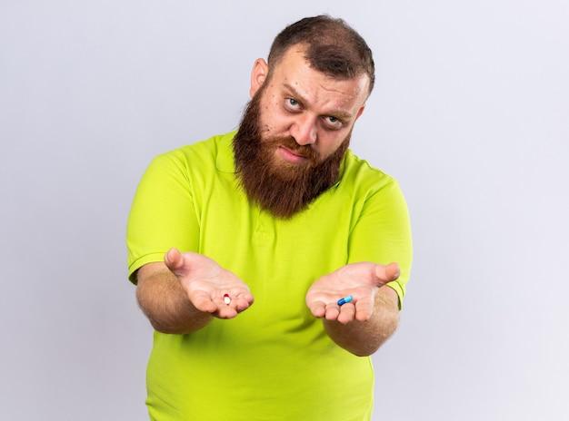 Uomo barbuto malsano in polo gialla con in mano diverse pillole che si sentono male e soffrono di influenza