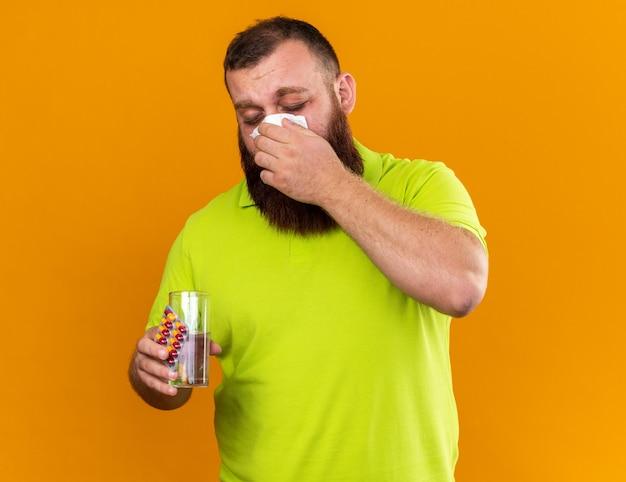 Uomo barbuto malsano in polo gialla con in mano un bicchiere d'acqua e pillole sentendosi terribilmente soffiando il naso nel tessuto che soffre di freddo in piedi sul muro arancione