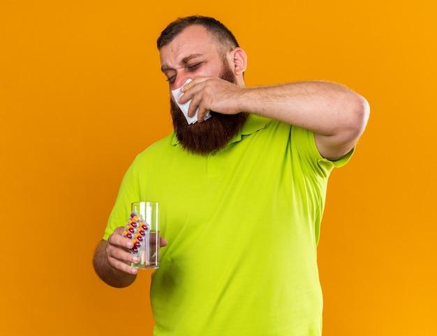 Uomo barbuto malsano in polo gialla con in mano un bicchiere d'acqua e pillole sensazione terribile che soffia il naso che cola starnuti nel tessuto soffre di freddo in piedi sul muro arancione
