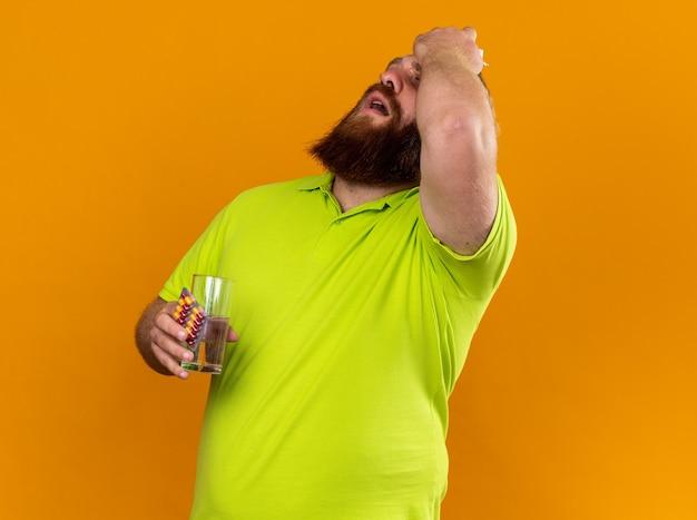 Uomo barbuto malsano in polo gialla con in mano un bicchiere d'acqua e pillole sentendosi terribilmente soffrendo di febbre fredda e forte mal di testa in piedi sul muro arancione