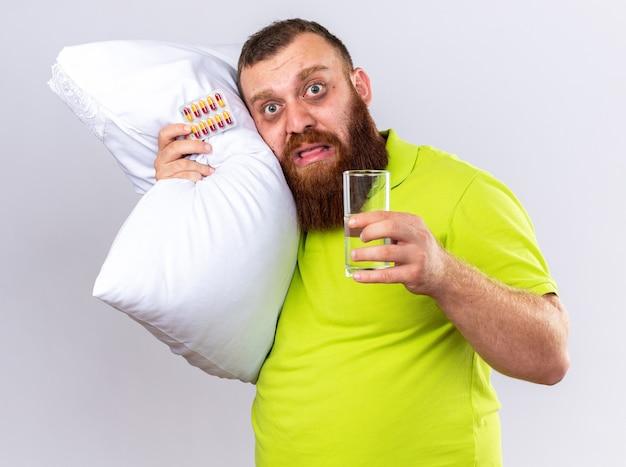 Uomo barbuto malsano in polo gialla con cuscino che tiene in mano un bicchiere d'acqua e pillole sensazione di malessere affetto da influenza che sembra preoccupato in piedi sul muro bianco