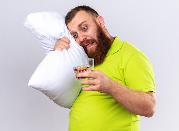 Uomo barbuto malsano in polo gialla con cuscino che tiene in mano un bicchiere d'acqua e pillole sentirsi male soffrendo di influenza in piedi sul muro bianco
