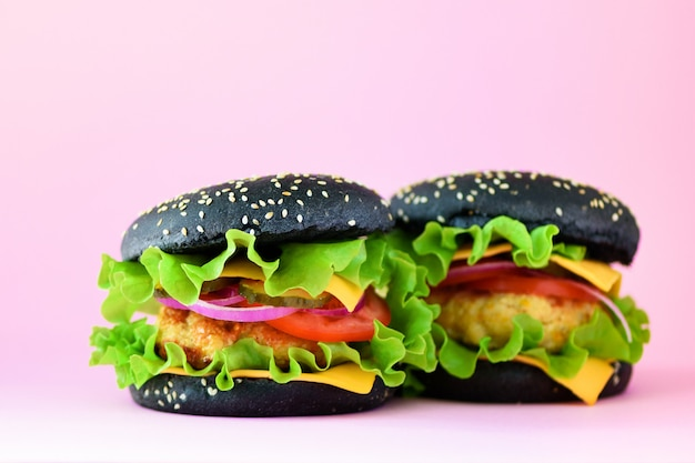 Unhealthy black burgers with beef, cheese, lettuce, onion, tomatoes on pink background. take away meal. unhealthy diet concept and copy space