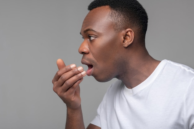Unhealthy breathing. close-up face of sad dark-skinned man with palm near his open mouth in studio on light background