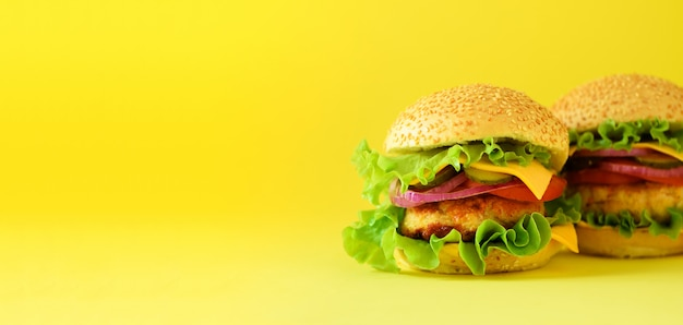 Unhealthy burgers with beef, cheese, lettuce, onion, tomatoes on yellow background. take away meal. unhealthy diet concept.