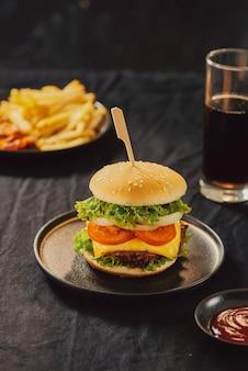 Нездоровая концепция. нездоровая пища: бургер, соус, картофель, кола.