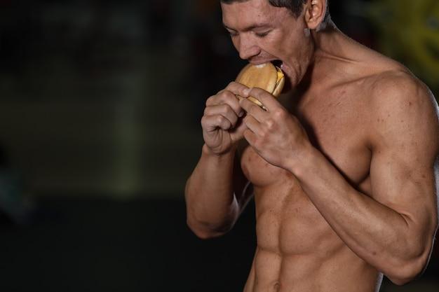 Концепция нездоровой диеты, мускулистый спортсмен-мужчина ест гамбургер. плохая диета или спорт, выбор образа жизни