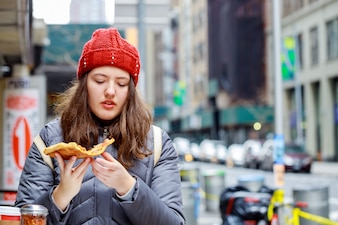 Unhealthy eating and street food pretty girl teenager, with cute, with piece of tasty pizza