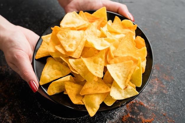 Нездоровые закуски быстрого питания. вредные привычки в еде. женщина руки, держа хрустящие вкусные чипсы начо на тарелке.