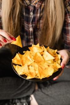 Нездоровые закуски быстрого питания. вредные привычки в питании. женщина ест хрустящие вкусные чипсы начо