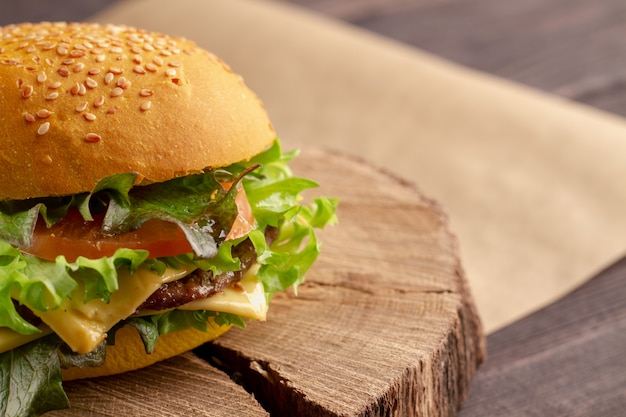 Unhealthy fatty burger with meat, cheddar cheese, lettuce. fast appetizing street burger