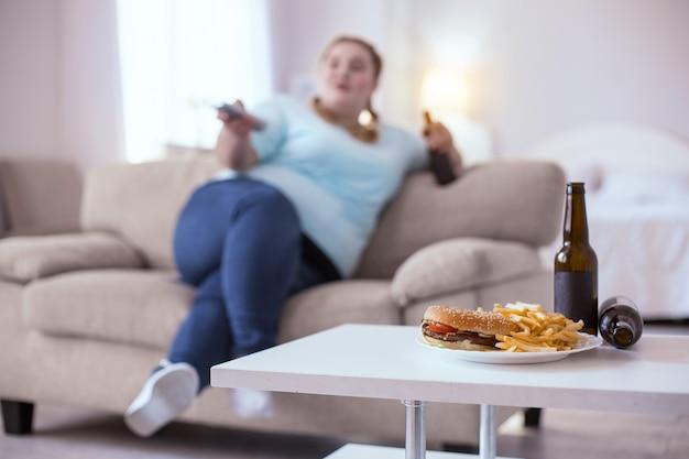 건강에 해로운 음식. 식사를 기다리는 테이블에 서있는 기름기 많은 정크 푸드