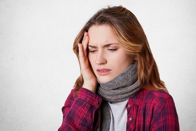 不健康な病気の女性はひどい頭痛を感じ、頭に手をかざし、暖かいニットスカーフとカジュアルな服を着ています