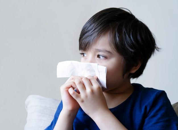 乾燥肌が鼻をティッシュに吹きつけている不健康な子供、鼻水やくしゃみに苦しんでいる子供、季節が変わると男の子が風邪をひく、子供の頃にティッシュで鼻を拭く
