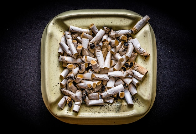 Unhealthy lifestyle - ashtray full of stump of cigarettes on dark background