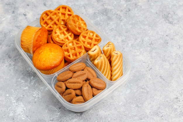 Unhealthy lunch box with cookies,waffles.muffins on concrete surface