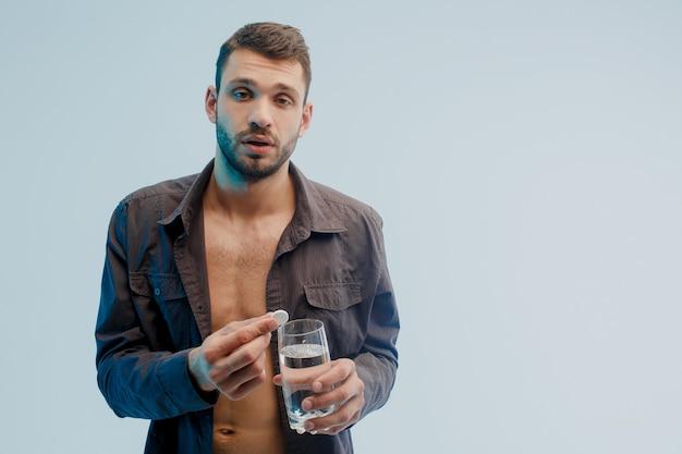 不健康な男は水と一緒にガラスに錠剤を投げ、クローズアップ。頭痛のある若いヨーロッパのひげを生やした男。ターコイズブルーの光で灰色の背景に分離。スタジオ撮影。コピースペース