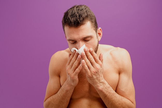 Unhealthy man using handkerchief for running nose. young european bearded guy is sick and sneezes. isolated on purple background. studio shoot. copy space