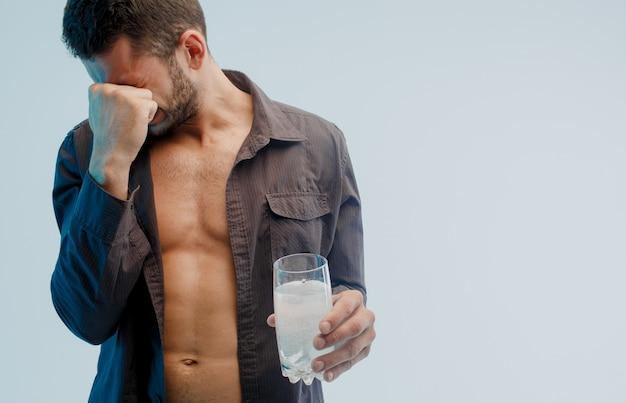 頭痛のある不健康な男性は、錠剤が溶けるとガラスを保持します。若いあごひげを生やした男は顔に触れます。ターコイズブルーの光で灰色の背景に分離。スタジオ撮影。コピースペース