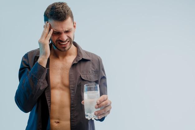 頭痛のある不健康な男性は、錠剤が溶けるとガラスを保持します。若いヨーロッパのひげを生やした男。ターコイズブルーの光で灰色の背景に分離。スタジオ撮影。コピースペース