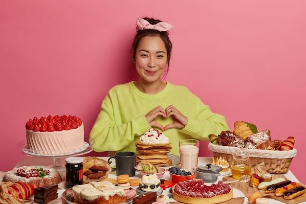 Нездоровое питание и калорийность. симпатичная азиатская девушка лепит сердечко над грудью, пробует свежеиспеченные домашние кондитерские изделия.