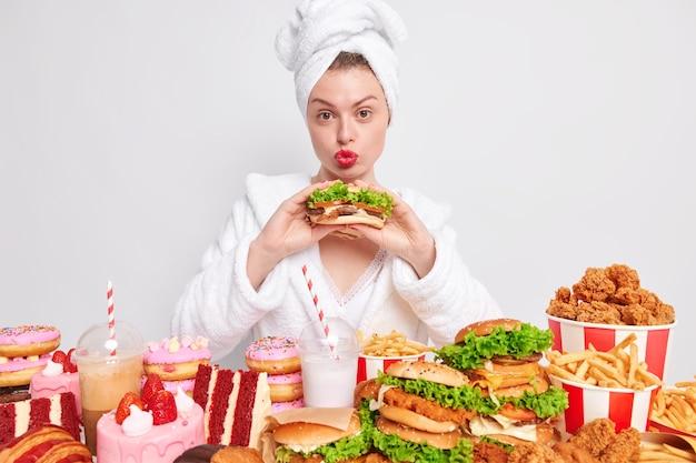 건강에 해로운 영양 체중 감량 다이어트와 폭식 개념. 사랑스러운 주부는 입술을 동그랗게 유지하고 맛있는 식욕을 돋우는 샌드위치를 먹습니다