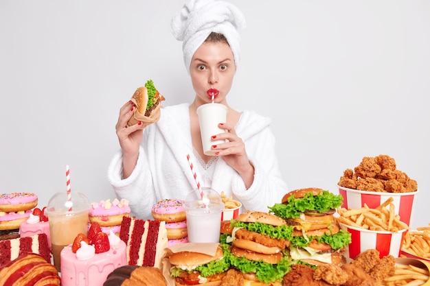 건강에 해로운 영양 개념입니다. 머리에 소다를 마시는 국내 목욕 가운 타월에 빨간 매니큐어와 입술을 가진 주부는 정크 푸드를 먹습니다