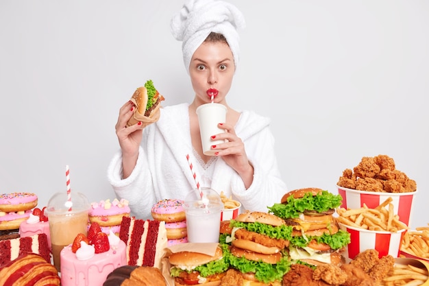Unhealthy nuttrition concept. housewife with red manicure and lips in domestic bathrobe towel on head drinks soda eats junk food