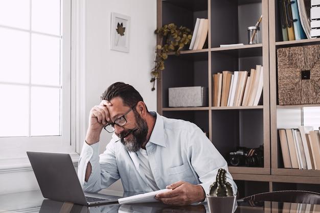 건강에 해로운 노년의 스트레스를 받는 사업가는 노트북을 보고, 컴퓨터를 사용하고, 일을 너무 많이 하거나 컴퓨터 과로로 고통받습니다.