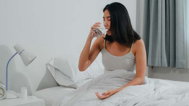 Unhealthy sick indian female suffers from insomnia. asian young woman taking painkiller medicine to relieve headache pain and drink glass of water sitting on bed in her bedroom at home in morning.