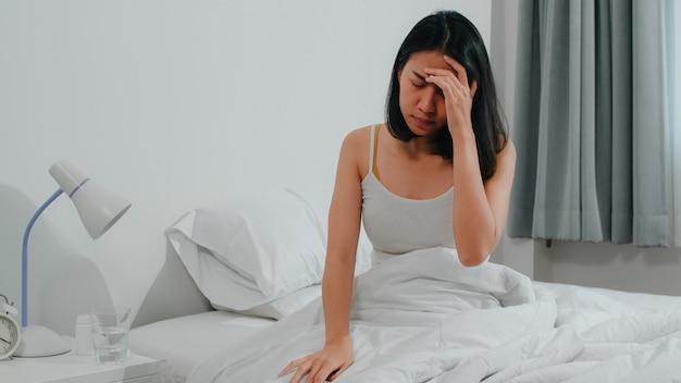 Нездоровая больная индийская женщина страдает бессонницей. азиатская молодая женщина принимает обезболивающее лекарство для облегчения головной боли и выпить стакан воды, сидя на кровати в своей спальне у себя дома в первой половине дня.
