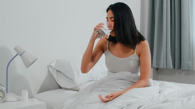 不健康な病気のインドの女性は不眠症に苦しんでいます。アジアの若い女性が鎮痛剤を服用して頭痛の痛みを和らげ、朝は自宅の寝室のベッドの上に座って水を飲みます。