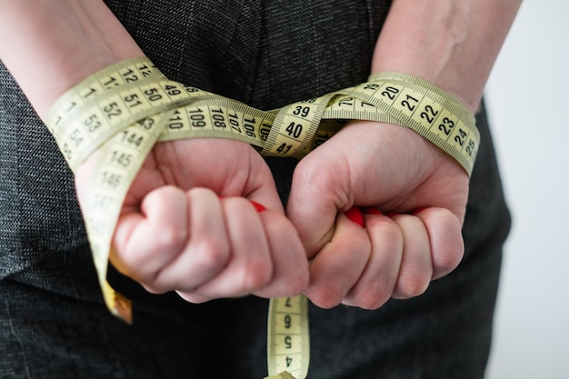 Unhealthy slimming methods. woman hands tied with measuring tape behind her back