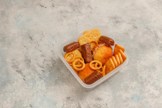 Unhealthy snacks on grey concrete
