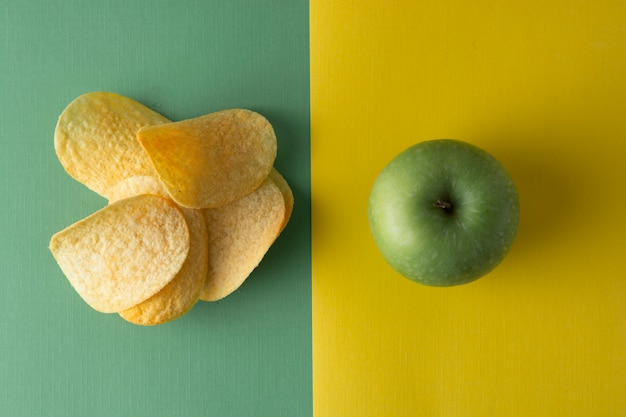 Unhealthy versus healthy food. choise . potatoe chips or green apple for snack. top view, colorful .