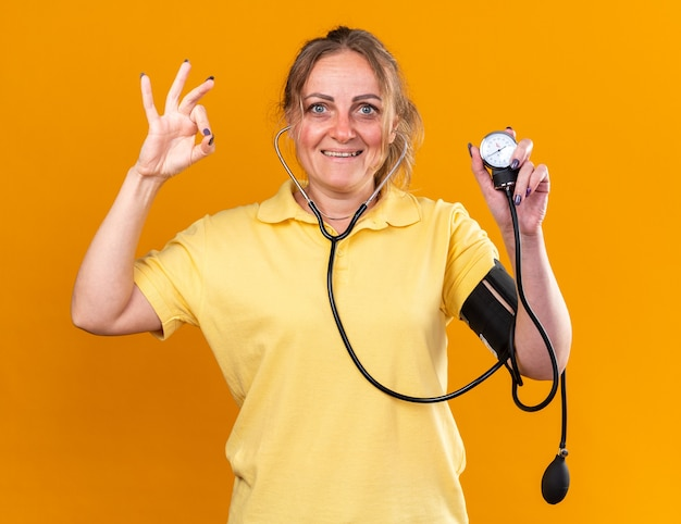 黄色いシャツを着た不健康な女性が、オレンジ色の壁の上に立っている ok サインを示す眼圧計の笑顔を使って血圧を測定している