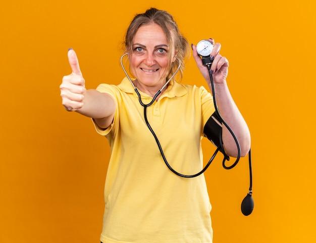 Нездоровая женщина в желтой рубашке чувствует себя лучше, измеряя свое кровяное давление с помощью тонометра, улыбаясь показывает палец вверх, стоя над оранжевой стеной
