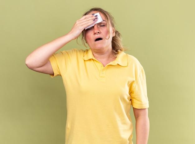 노란색 셔츠에 건강에 해로운 여자가 독감과 발열이있는 조직으로 이마를 닦는 끔찍한 느낌
