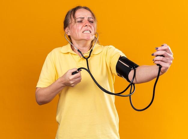 Нездоровая женщина в желтой рубашке, которая плохо себя чувствует, страдает от гриппа и простуды, измеряет свое кровяное давление с помощью тонометра и выглядит обеспокоенной, стоя у оранжевой стены