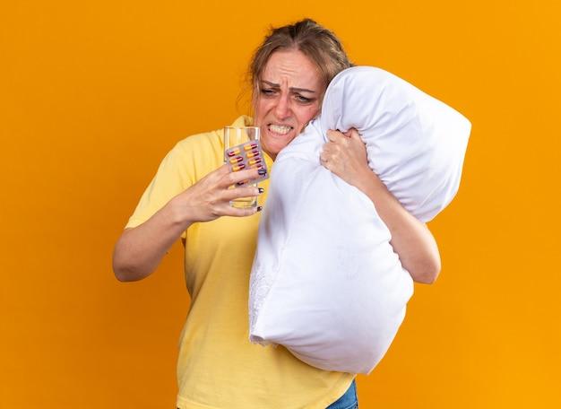 독감과 감기로 고통받는 노란색 셔츠에 건강에 해로운 여자가 약과 물 잔을 들고 몸이 안아주는 베개를 들고 짜증이 나고 오렌지 벽 위에 서서 실망했습니다.