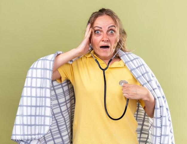 Donna malsana avvolta in una coperta che si sente male soffre di influenza e raffreddore ascoltando il suo battito cardiaco usando lo stetoscopio che sembra preoccupata in piedi sul muro verde
