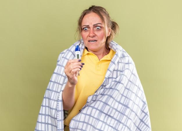 독감과 감기 들고 온도계로 끔찍한 고통을 느끼는 담요에 싸여 건강에 해로운 여자가 녹색 벽 위에 서있는 것을 두려워합니다.
