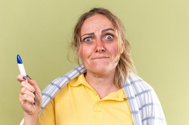 독감과 감기 들고 온도계로 고통받는 끔찍한 담요에 싸여 건강에 해로운 여자는 녹색 벽 위에 서있는 걱정을 찾고 있습니다.